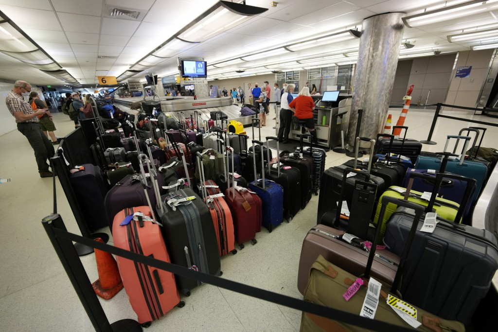 Baggage stacks up from delayed travellers in the baggage claim area in Denver International Airport Wednesday, June 16, 2021, in Denver.  The Biden ad...