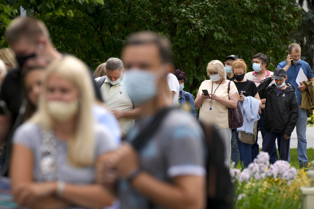 People wait in line to recieve a coronavirus vaccine at a vaccination center  in the VDNKh (The Exhibition of Achievements of National Economy) in Mos...