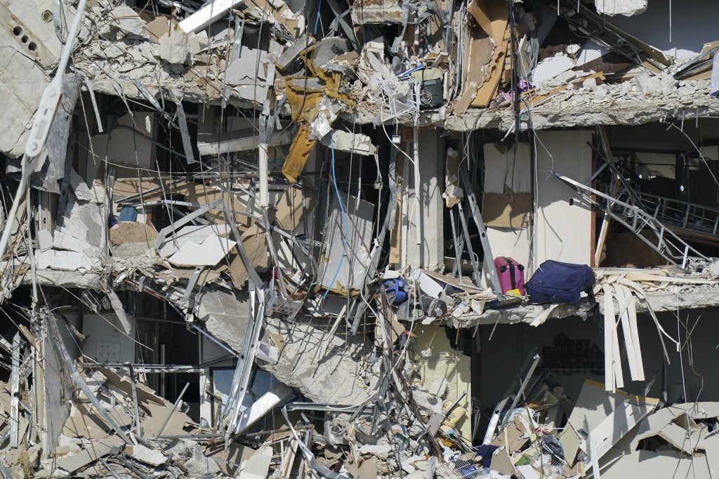 Personal belongings are seen amid debris dangling from the remains of apartments sheared in half, in the still standing portion of the Champlain Tower...
