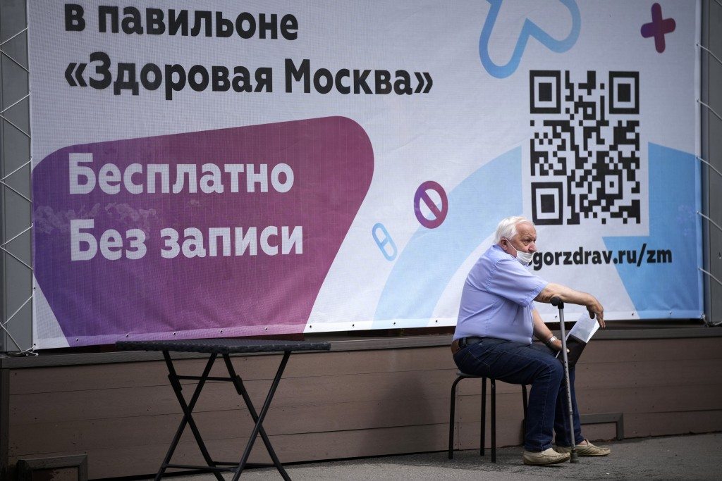 An elderly man sits waiting in line to get a coronavirus vaccine at a vaccination center at VDNKh (The Exhibition of Achievements of National Economy)...