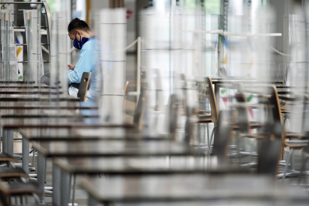 A Tokyo 2020 Olympic staff member rests at a food court at Main Press Center (MPC) for Tokyo 2020 Olympic Games at Tokyo Big Site Friday, July 2, 2021...