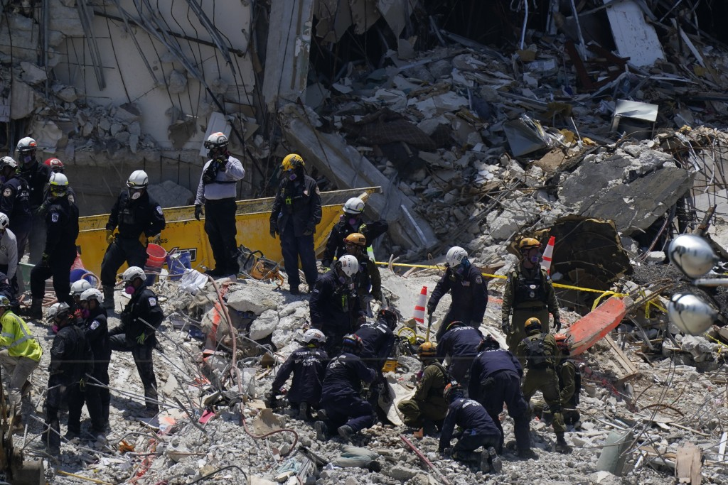 Search and rescue personnel work atop the rubble at the Champlain Towers South condo building, where scores of victims remain missing more than a week...