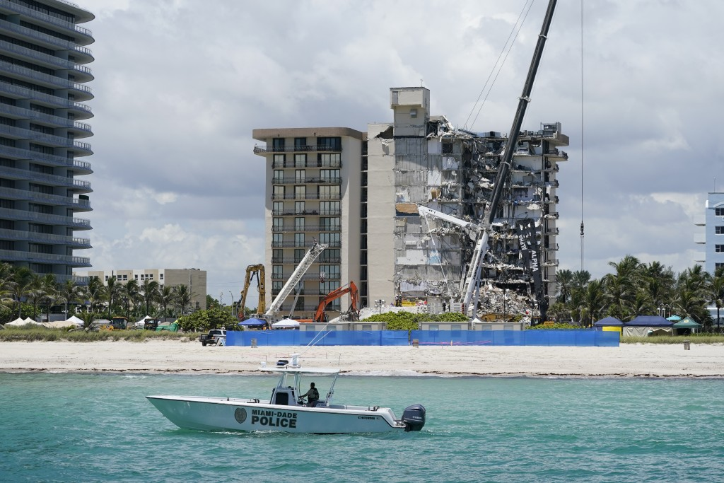 A Miami-Dade County Police boat patrols in front of the Champlain Towers South condo building, where search and rescue efforts continue more than a we...