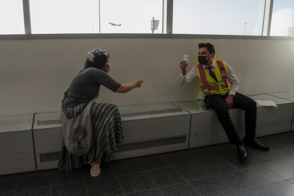 Elissa Montanti, founder and director of the Global Medical Relief Fund, hands her card to an Emirates airline employee while waiting for amputee chil...