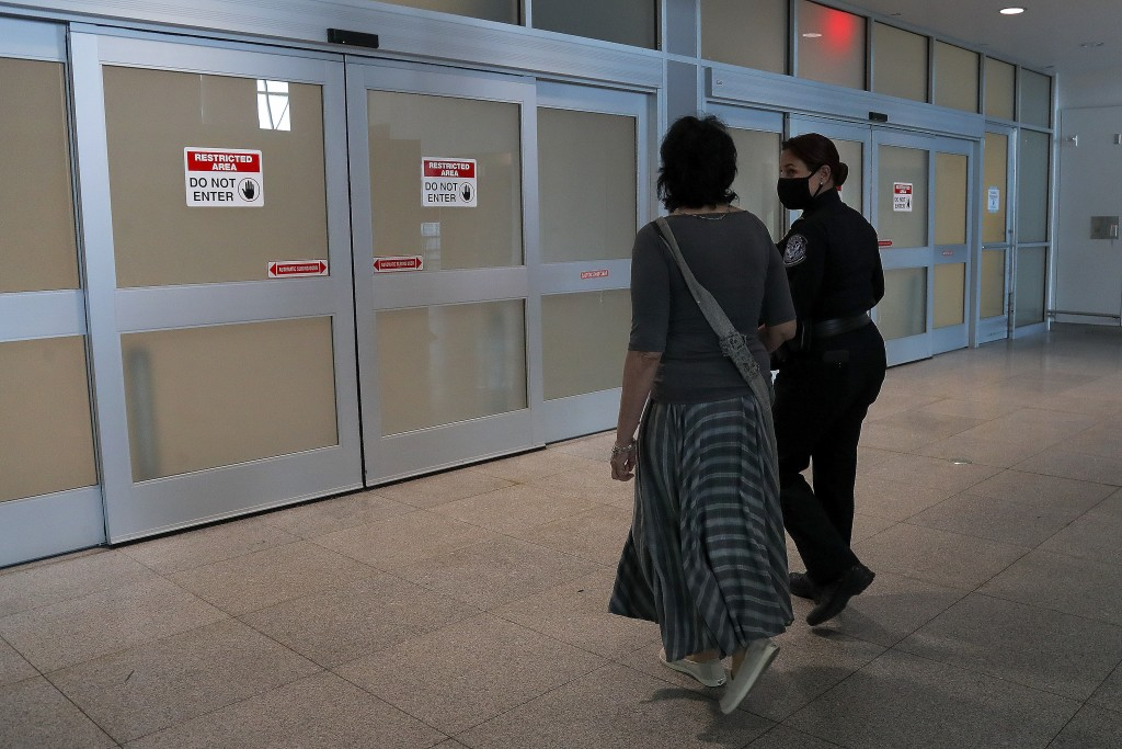 Kerry Mitchell, a supervisory officer for Customs and Border Protection, right, escorts Elissa Montanti into the passport control and baggage claim ar...