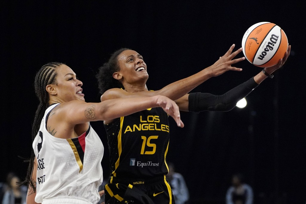 Los Angeles Sparks guard Brittney Sykes, right, shoots as Las Vegas Aces center Liz Cambage defends during the first half of a WNBA basketball game Fr...