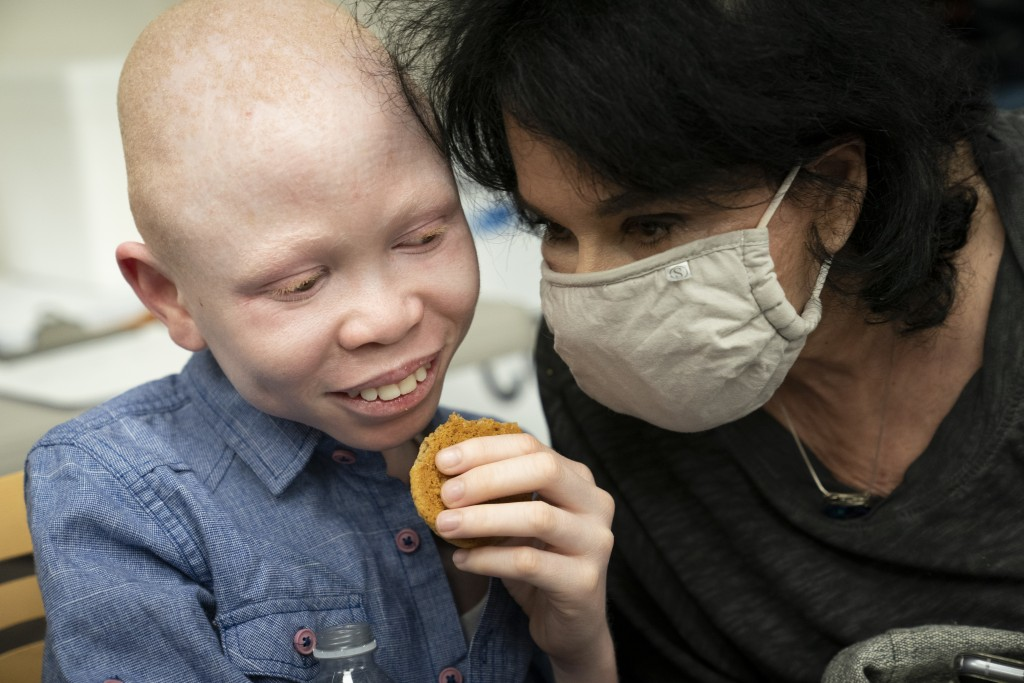 Baraka Cosmas, 12, has a cookie and relaxes with Elissa Montanti, founder and director at The Global Medical Relief Fund, left, after receiving a COVI...