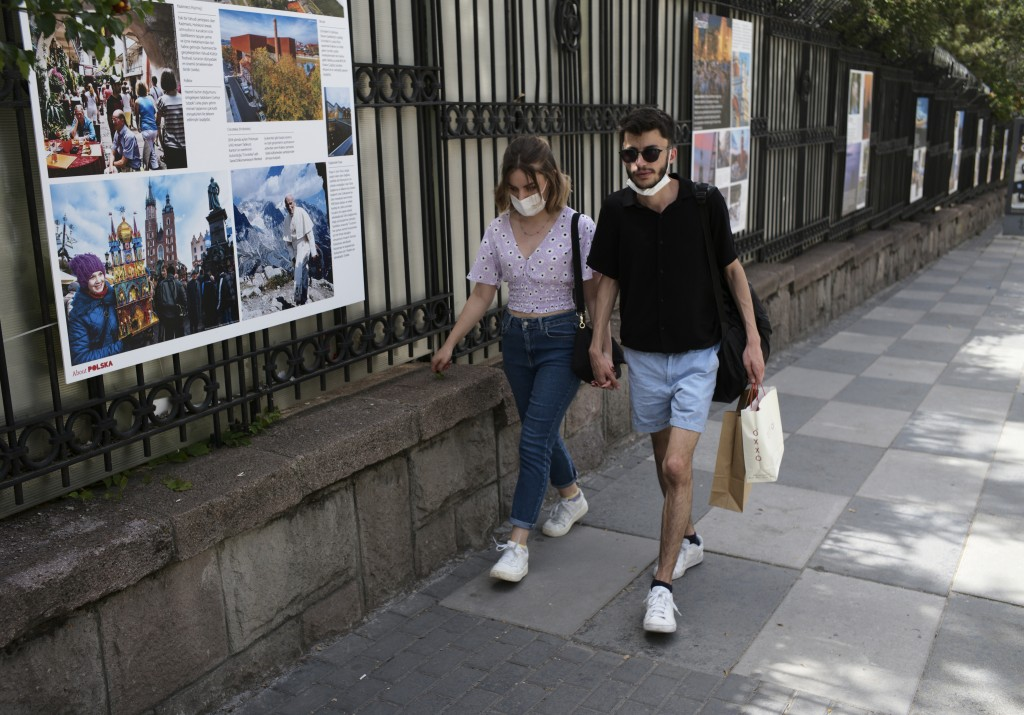A couple walk in the shadow as a temperature of 36 degrees celsius hits the Turkish capital, Ankara, Friday, July 2, 2021. Turkish health-care workers...