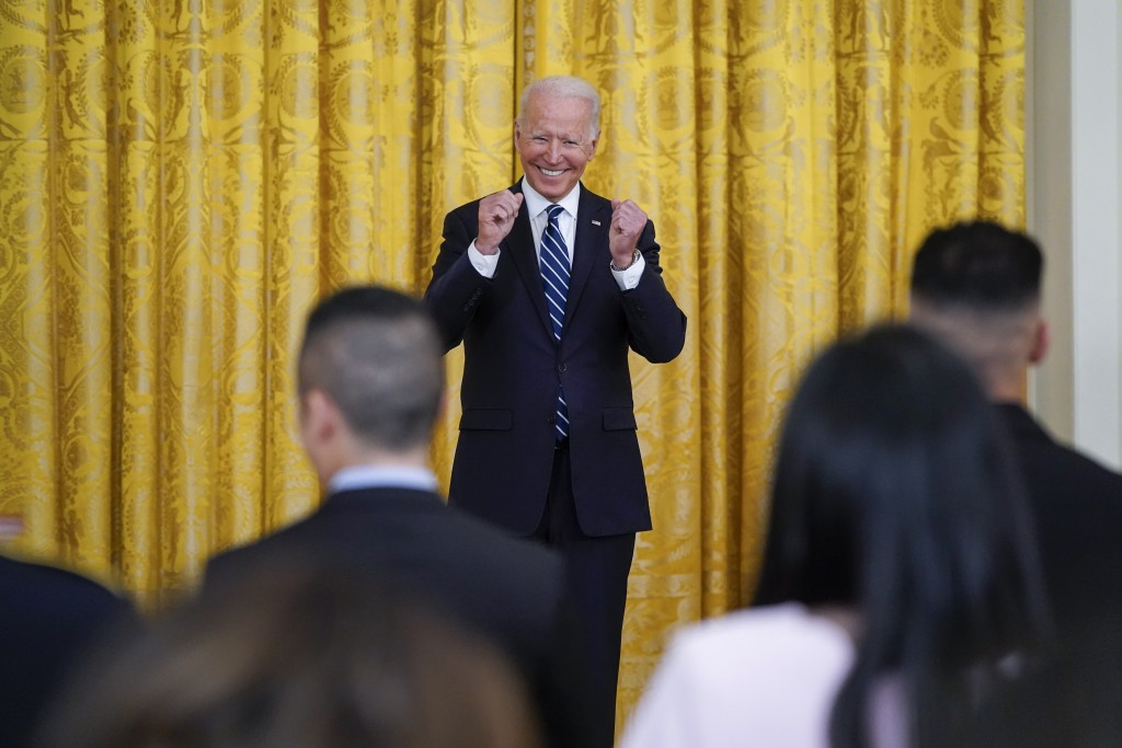 President Joe Biden smiles after people took the Oath of Allegiance during a naturalization ceremony in the East Room of the White House, Friday, July...