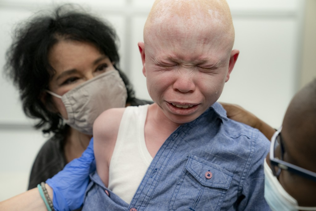 Baraka Cosmas, 12, cries on the lap of Elissa Montanti, founder and director at The Global Medical Relief Fund, left, after he receives a COVID-19 vac...