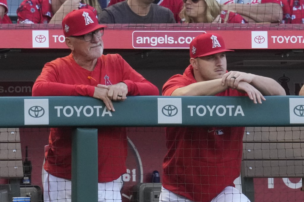 Los Angeles Angels manager Joe Maddon, left, and center fielder Mike Trout stand in the dugout during the third inning of a baseball game against the ...