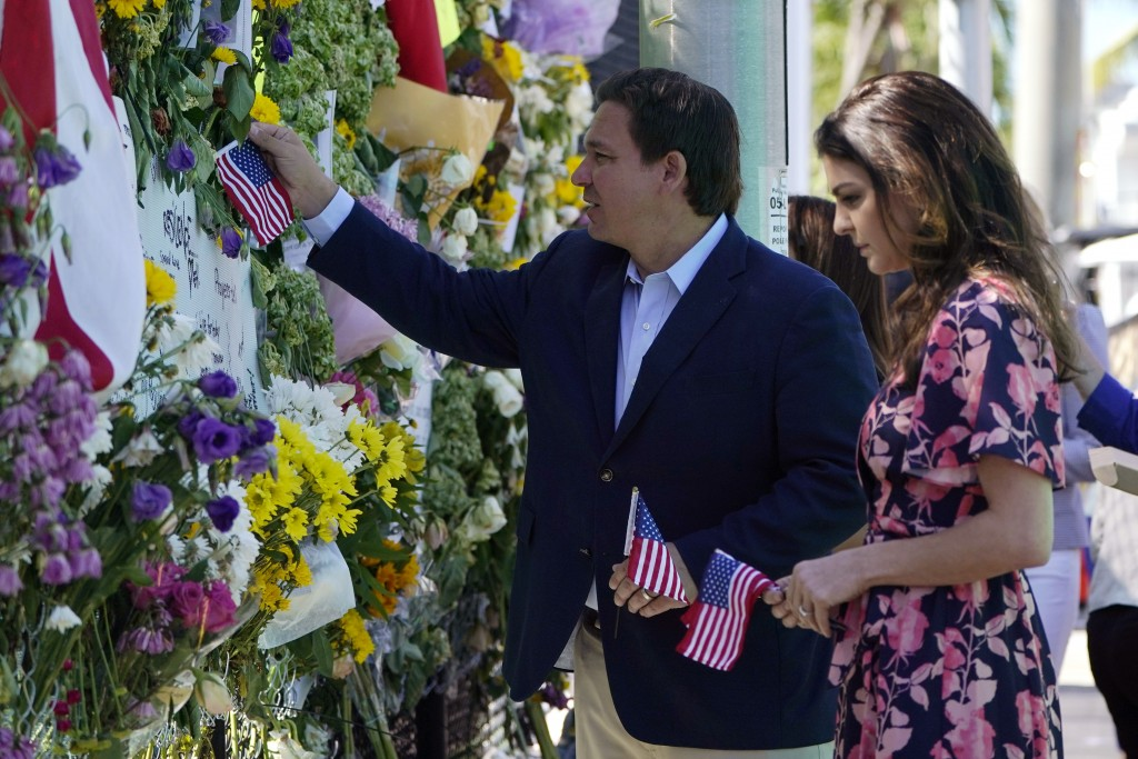 Florida Gov. Ron DeSantis, left, and his wife Casey leave flags at a makeshift memorial near the Champlain Towers South condo building, where scores o...