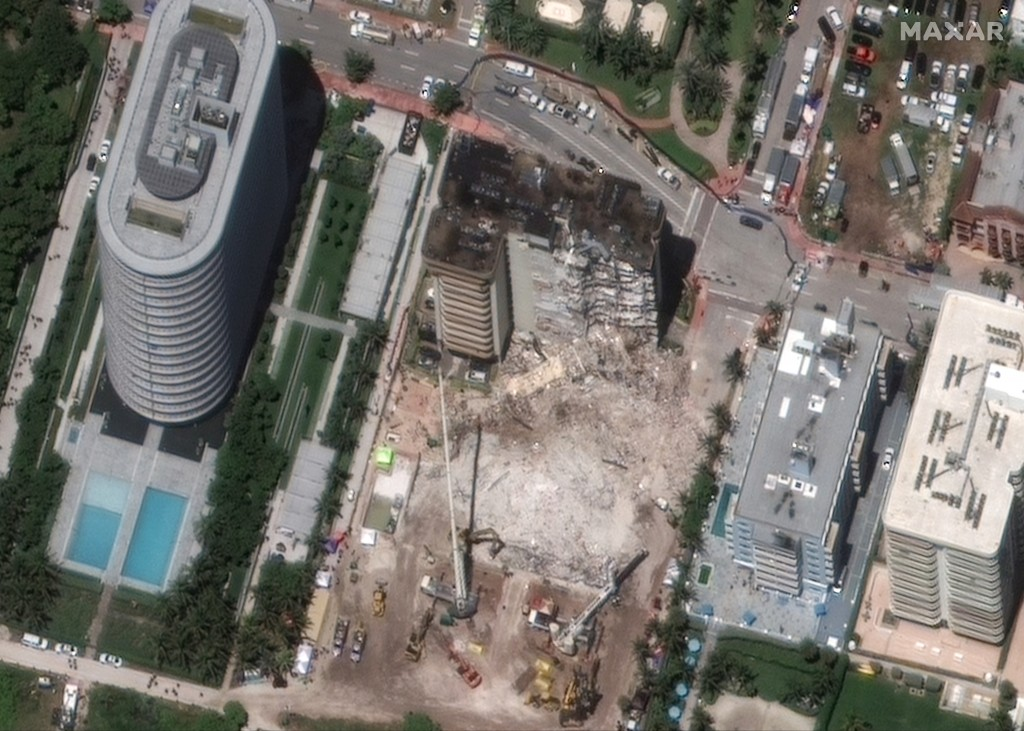 In this satellite image provided by Maxar Technologies heavy-lift cranes are used to aid in the search and recovery operation at the partially collaps...