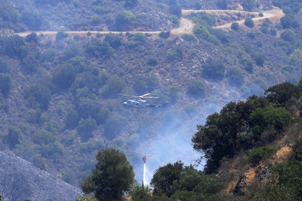 An helicopter drops water over the mountain of Troodos in Agious Vavatsinias village, southwestern Cyprus, Sunday, July 4, 2021. Cyprus search crews d...