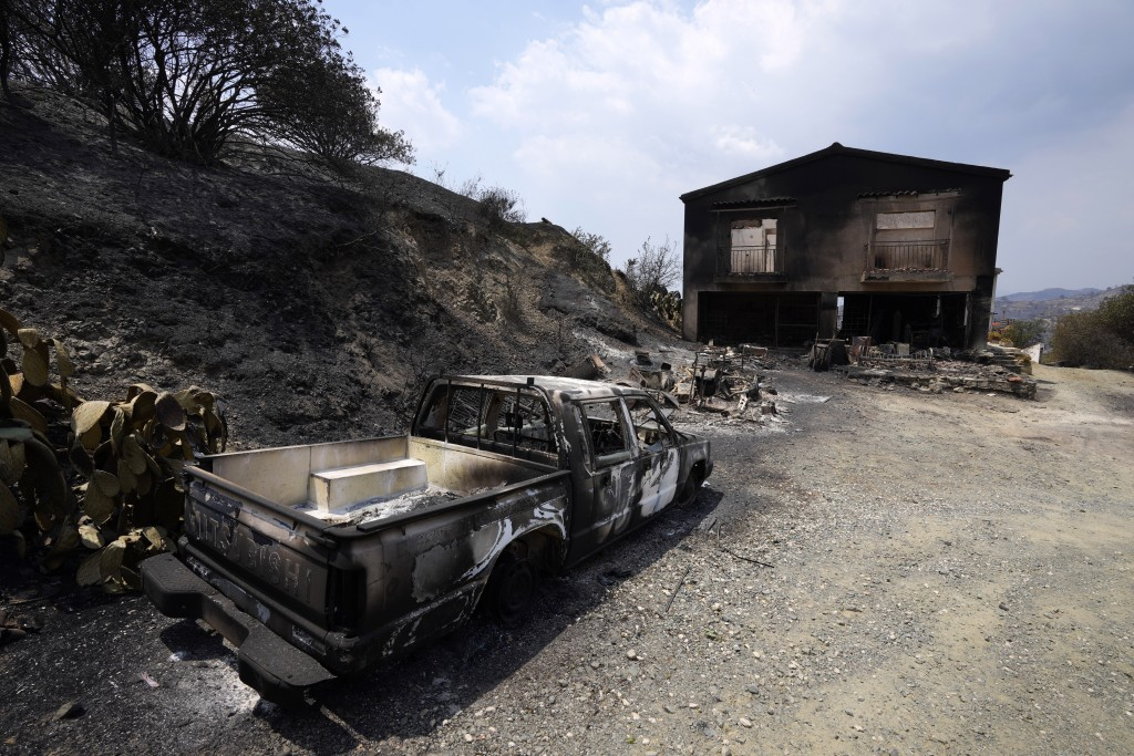 A burned car is seen outside a damaged house on Troodos mountain, in Ora village, southwestern Cyprus, Sunday, July 4, 2021. Cyprus search crews disco...