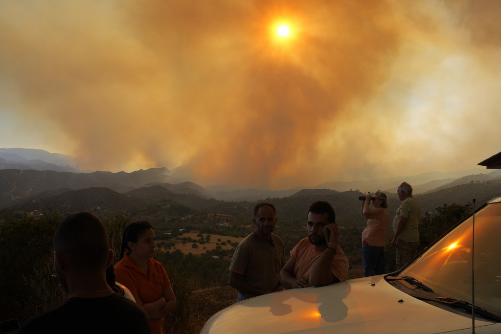 Residents of villages watch a fire in the Larnaca mountain region on Saturday, July 3, 2021. Cyprus has asked fellow European Union member states on S...
