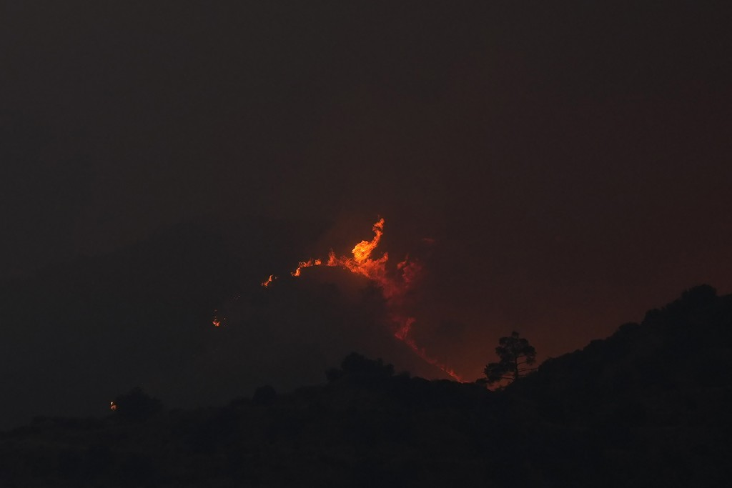 A view of flames from a fire  in the Larnaca mountain region, Saturday, July 3, 2021. Cyprus has asked fellow European Union member states on Saturday...