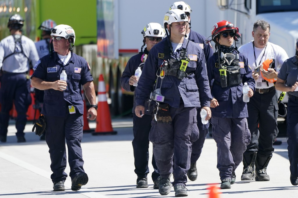 Members of the South Florida Urban Search and Rescue team walk near the Champlain Towers South condo building, where scores of victims remain missing ...