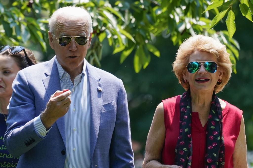 President Joe Biden eats a cherry as he tours King Orchards fruit farm Sen. Debbie Stabenow, D-Mich., Saturday, July 3, 2021, in Central Lake, Mich. (...