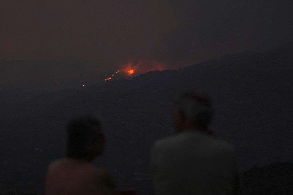 Residents of  avillage watch a fire in the Larnaca mountain region, Saturday, July 3, 2021. Cyprus has asked fellow European Union member states on Sa...
