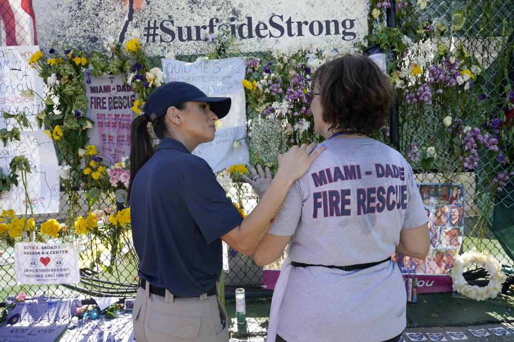Miami Beach police chaplain Omy Llaneras, left, stands with a woman at a makeshift memorial near the Champlain Towers South condo building, where scor...