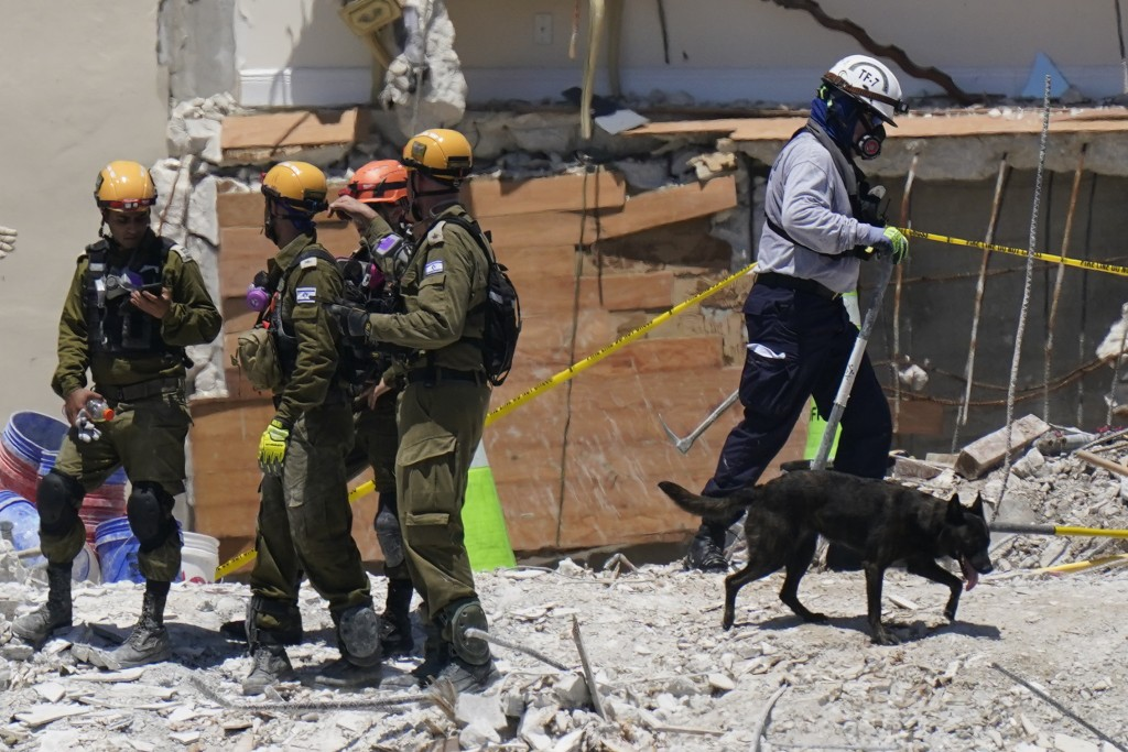 FILE - In this July 2, 2021, file photo, a dog aiding in the search walks past a team of Israeli search and rescue personnel, left, atop the rubble at...