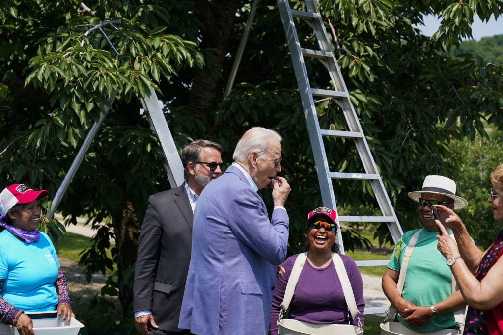 President Joe Biden eats a freshly picked cherry from a bucket while meeting with workers as he tours King Orchards fruit farm with Sen. Gary Peters, ...