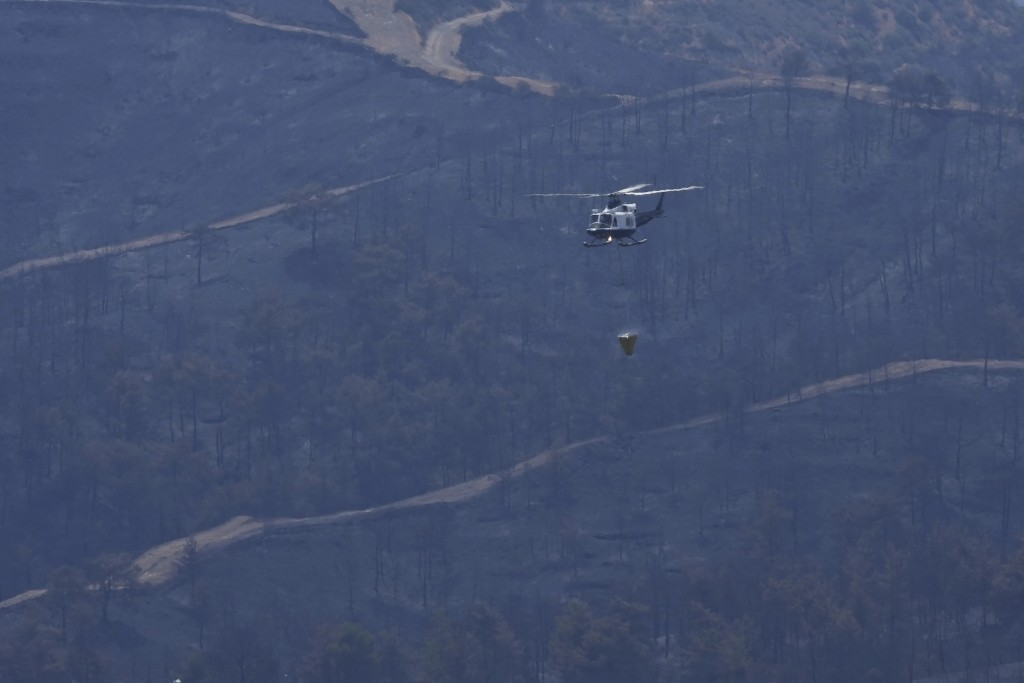 An helicopter flies over the burned mountain of Troodos in Agious Vavatsinias village, southwestern Cyprus, Sunday, July 4, 2021. Cyprus search crews ...