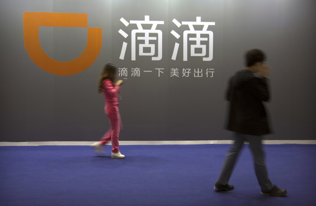 FILE - In this April 27, 2017, file photo, visitors walk past a sign for Chinese ride-hailing service Didi Chuxing at the Global Mobile Internet Confe...