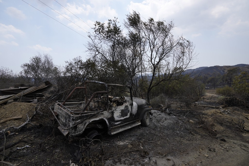 A burned car is seen on Troodos mountain, in Ora village, southwestern Cyprus, Sunday, July 4, 2021. Cyprus search crews discovered the bodies of four...