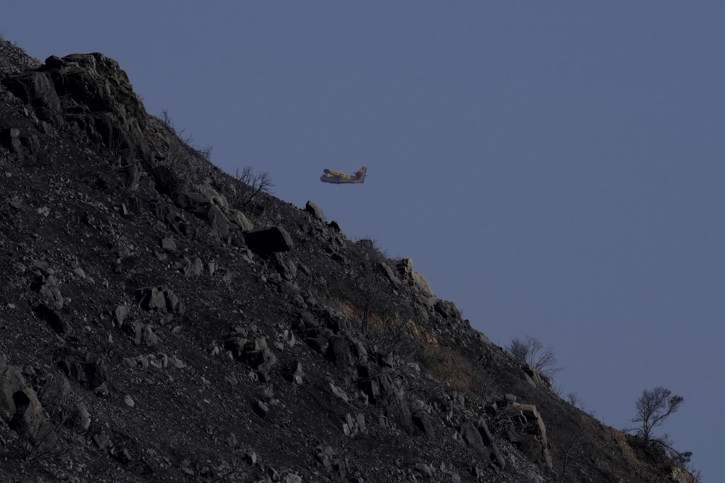 A canadair flies over the burned Larnaca mountain region near Ora village, Cyprus, Sunday, July 4, 2021. Cyprus' interior minister says four people ha...