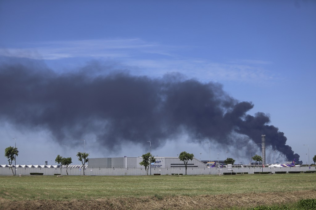 Smoke billows high into the air behind the Suvarnabhumi Airport in the Samut Prakan province, Thailand, Monday, July 5, 2021. A massive explosion at a...