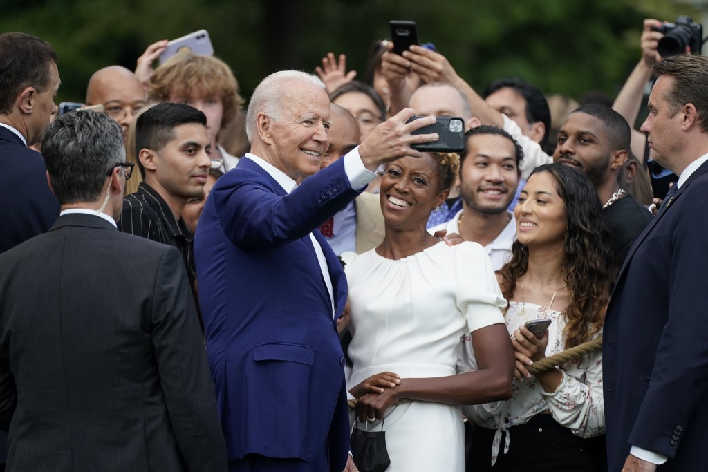 President Joe Biden poses for a photo with attendees during an Independence Day celebration on the South Lawn of the White House, Sunday, July 4, 2021...
