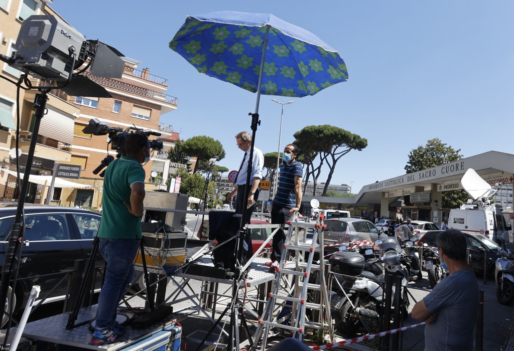 Media gather outside of the Gemelli Polyclinic, where Pope Francis was hospitalized Sunday, in Rome, Monday, July 5, 2021. Pope Francis was spending h...