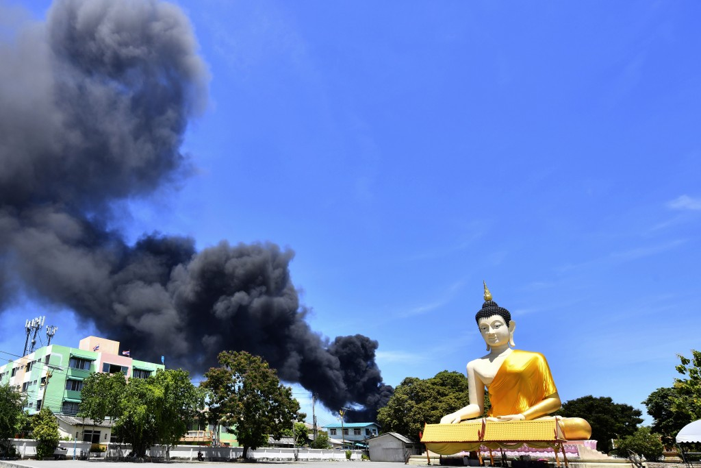 Rising smoke is seen behind the giant Buddha statue in Samut Prakan province, Thailand, Monday, July 5, 2021. A massive explosion at a factory on the ...