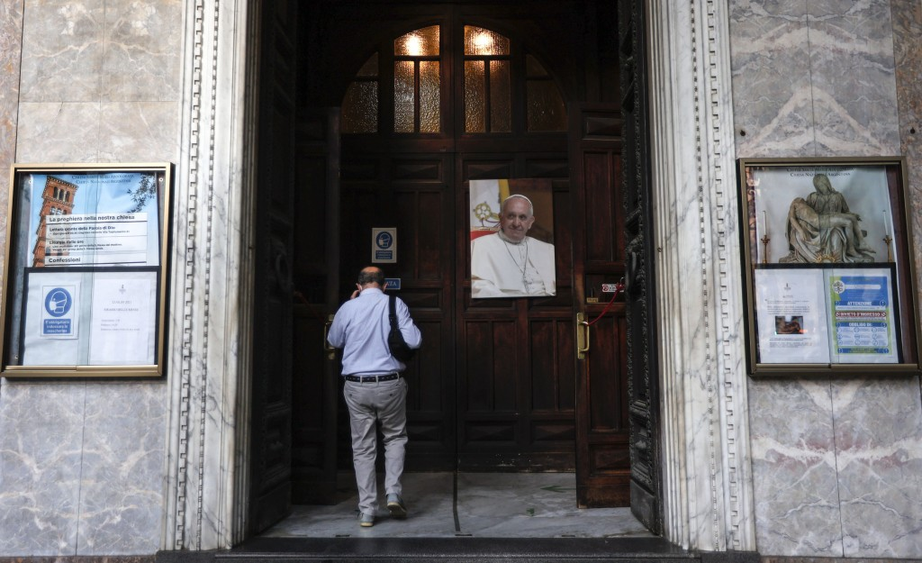 A man passes past a portrait of Pope Francis as he enters the Argentine church of Santa Maria Addolorata (Our Lady of Sorrows) in Rome, Sunday, July 4...