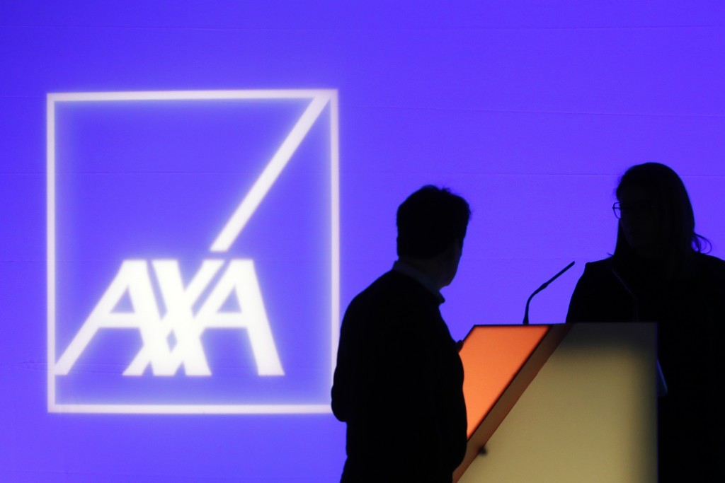 FILE - In this Feb. 21, 2019, file photo, people stand in front of the logo of AXA Group prior to the company's 2018 annual results presentation, in P...