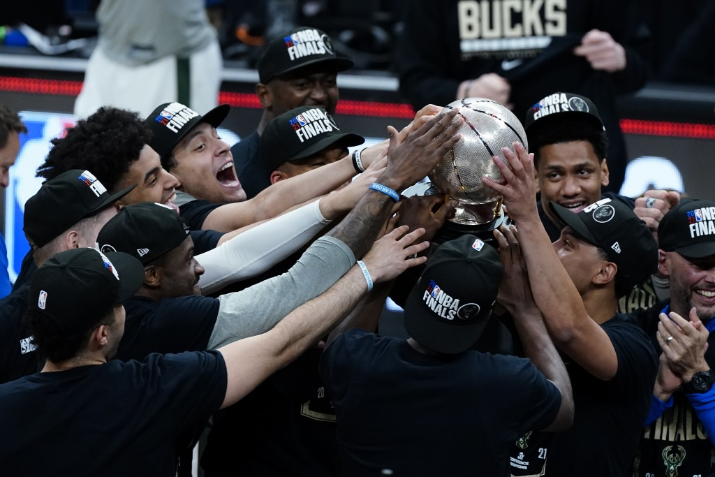 The Milwaukee Bucks hoist the trophy after defeating the Atlanta Hawks in Game 6 of the Eastern Conference finals in the NBA basketball playoffs and a...