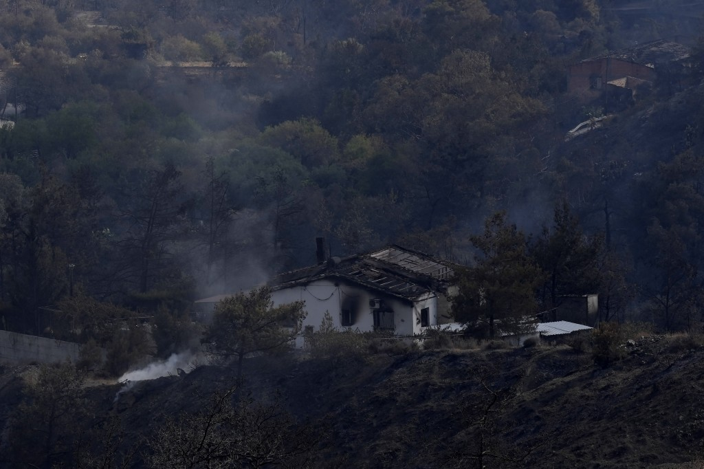 A burned house in Ora village, in Larnaca mountain region, Cyprus, Sunday, July 4, 2021. Cyprus' interior minister says four people have died in what ...