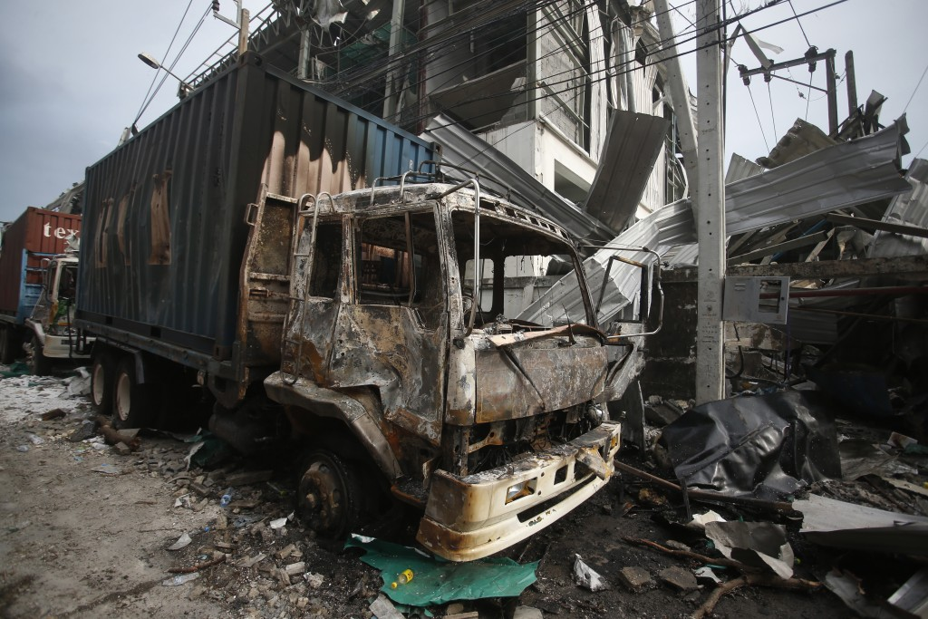 A charred truck sits in the wreckage after and explosion and raging fire at a chemical factory in Samut Prakan province, Thailand, Monday, July 5, 202...