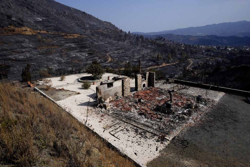 A view of a burnt house outside of Ora village, in the background is the Larnaca mountain region, Cyprus, Sunday, July 4, 2021. Cyprus' interior minis...