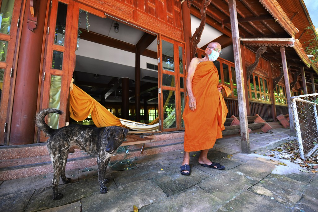 A Buddhist monk stands in front of a damage door after an explosion at King Kaeo Temple in Samut Prakan province, Thailand, Monday, July 5, 2021. A ma...