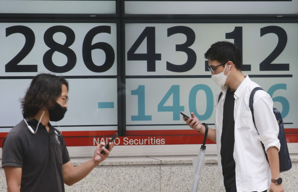 People walk by an electronic stock board of a securities firm in Tokyo, Monday, July 5, 2021.