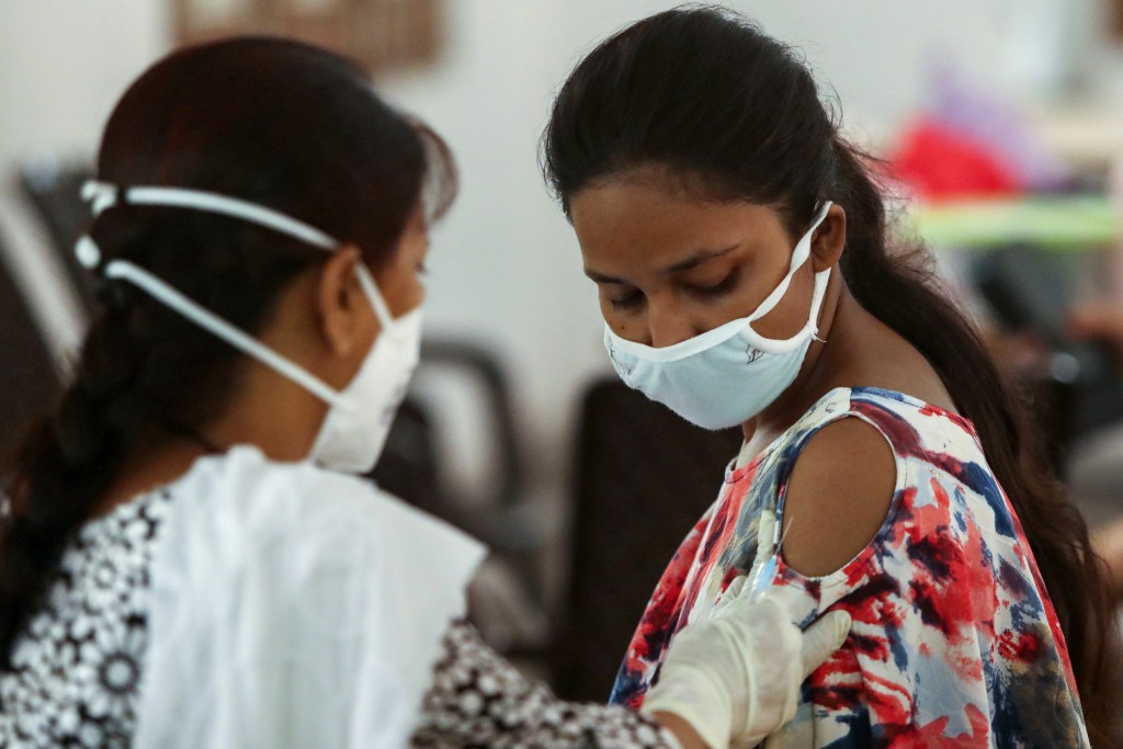 A girl receives a dose of coronavirus vaccine at a vaccination center in Jammu, India, Monday, June 5, 2021. (AP Photo/Channi Anand)