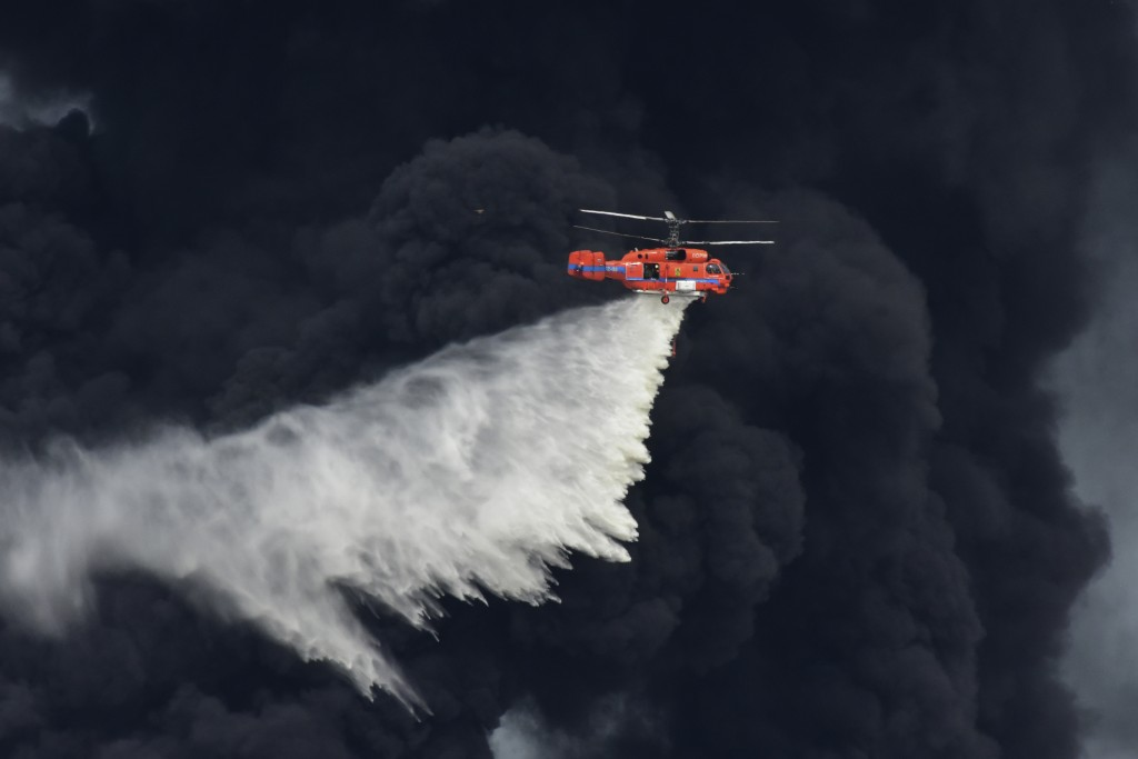 A helicopter drops a fire-retardant in a massive factory fire in Samut Prakan province, Thailand, Monday, July 5, 2021. A massive explosion at a facto...