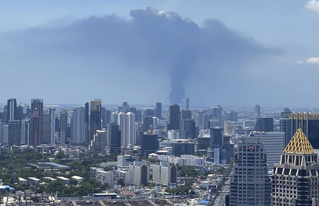 In a view from downtown Bangkok, giant plumes of smoke can be seen rising from the Samut Prakan province, Thailand, Monday, July 5, 2021. A massive ex...
