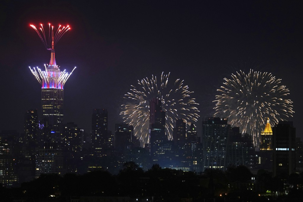 Fireworks explode from the Empire State Building and over the New York City skyline during Macy's 4th of July fireworks display, late Sunday, July 4, ...