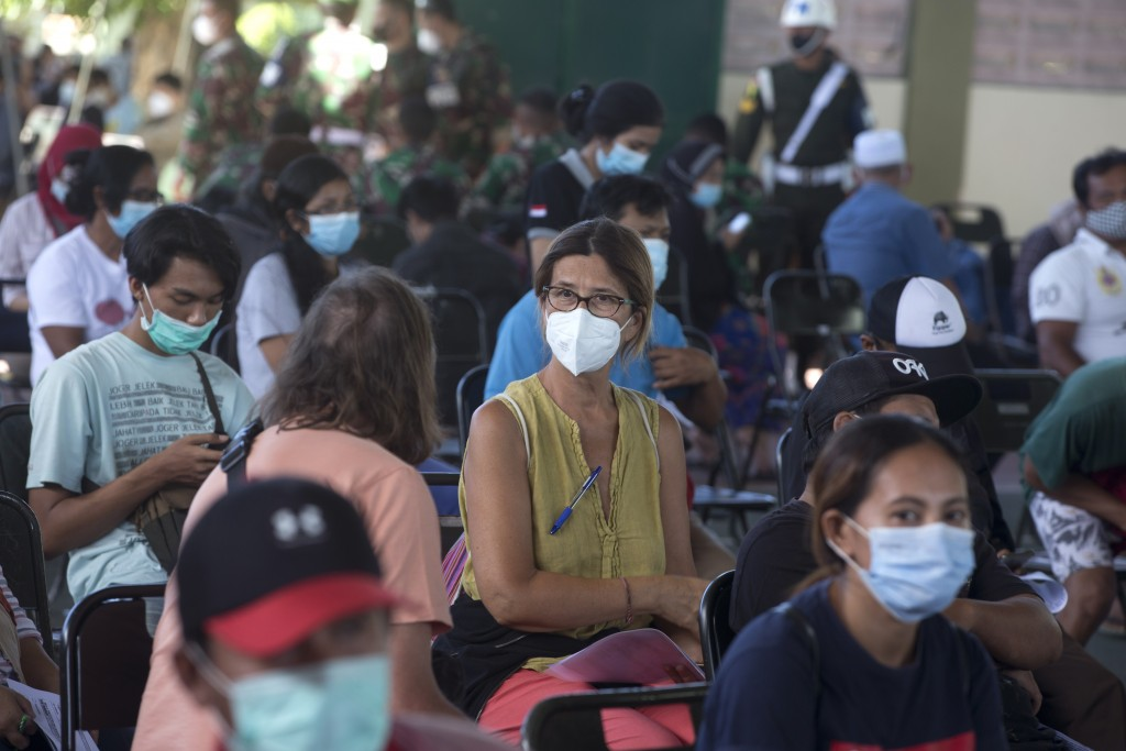 Foreign people wait to receive the AstraZeneca vaccine for COVID-19 during a vaccination campaign in Bali, Indonesia,Tuesday, July 6, 2021. (AP Photo/...