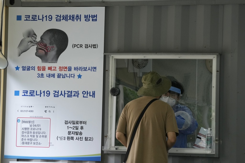 A medical worker in a booth takes a nasal sample from a man at a coronavirus testing site in Seoul, South Korea, Tuesday, July 6, 2021. The sign at le...