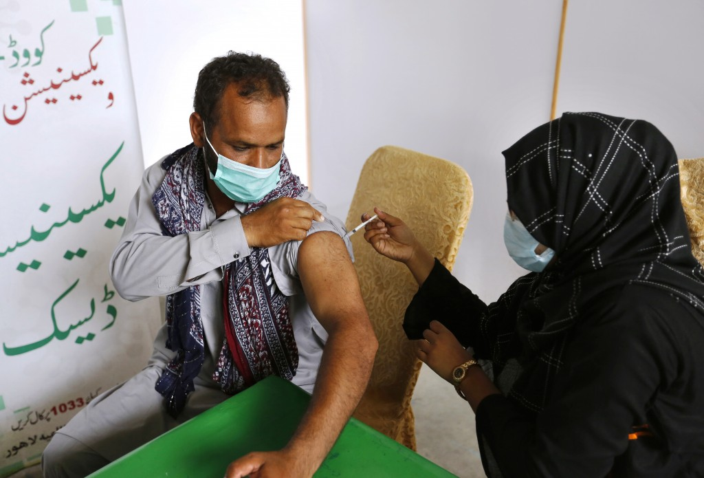 An expatriate worker receives the Moderna COVID-19 vaccine from a health worker at a vaccination center, in Lahore, Pakistan, Tuesday, July 6, 2021. N...